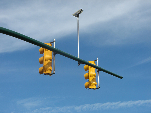 yellow traffic lights hang out into a blue sky