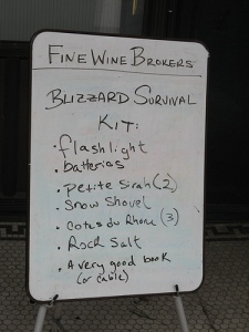 A sign listing things you need to survive a blizzard - flashlight, batteries, a good book, wine.