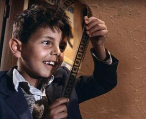 Little boy from Cinema Paradiso holding a piece of film.