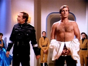 Still from Buck Rogers: Planet of the Amazon Women. Some government official shows off a shirtless Buck to potential buyers.