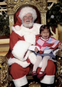 A little girl sits on Santa's lap, screaming.