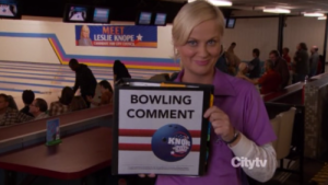 "Leslie Knope holding a big binder that says ""Bowling Comment"""