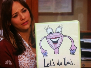 "Ann Perkins holds a binder with ""Let's Do This"" and a picture of a happy uterus."