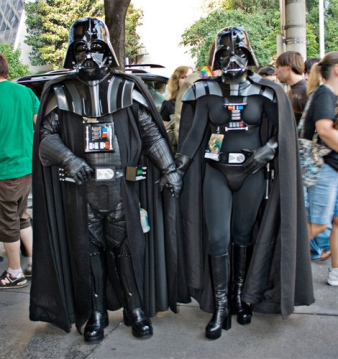 A man and woman dressed as Darth Vader holding hands on a crowded street.