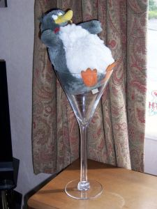 A stuffed toy penguin in a martini glass