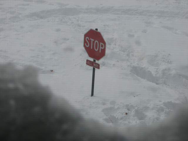 A stop-sign mostly submerged in snow.