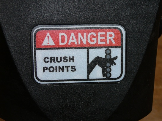 A warning sign: Danger Crush Points with a graphic of a hand getting crushed.