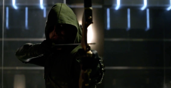 A still image from the show Arrow, where the character is shooting an arrow and has a hood pulled to hide his face.
