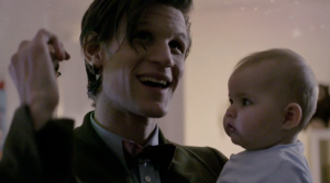 Matt Smith as The Doctor, holding a baby (Stormageddon)