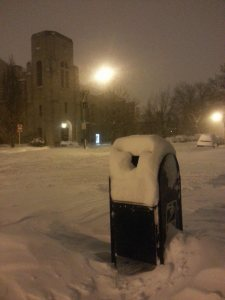 A mailbox and a church are covered with snow on a Chicago street.