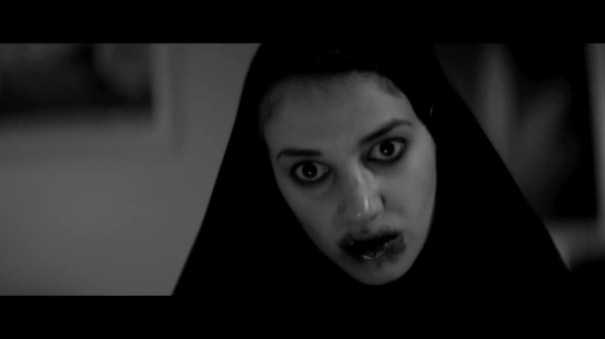 A still from A Girl Walks Home Alone At Night, where a young woman in a hijab has blood smeared around her mouth because (spoiler) she just ate a sexist dude.