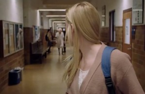 Screen shot from the horror film It Follows. A girl in a hallway looks back and sees an old woman in a hospital gown striding toward her.