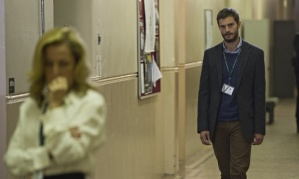 Paul Spector follows Stella Gibson down a hallway.