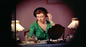 Judith Evelyn as Miss Lonelyhearts from Rear Window, wearing a vivid green dress and a black hat.
