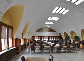 A beautiful space with arched ceilings, big windows, skylights, and rows of tables and chairs.