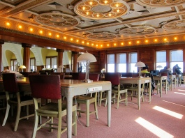 A beautiful space with an art deco ceiling, chairs, tables, lamps.